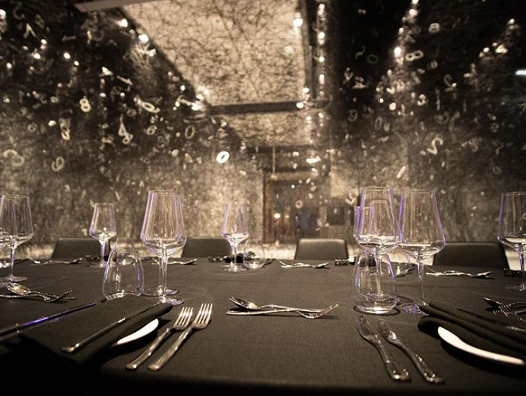 Photo of a table with a black tablecloth and silver cutlery and empty glasses, before an event. In the background is a vast artwork made of black wool