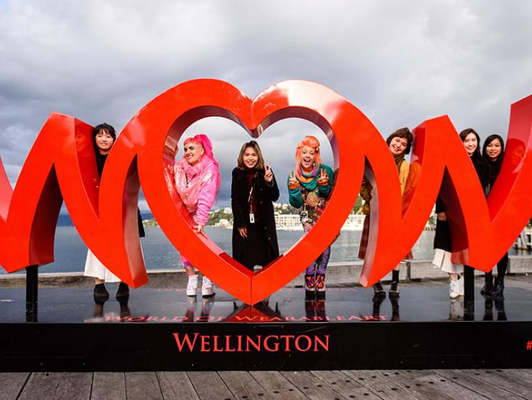 A group of women pose with a giant World of WearableArt logo on the Wellington waterfront