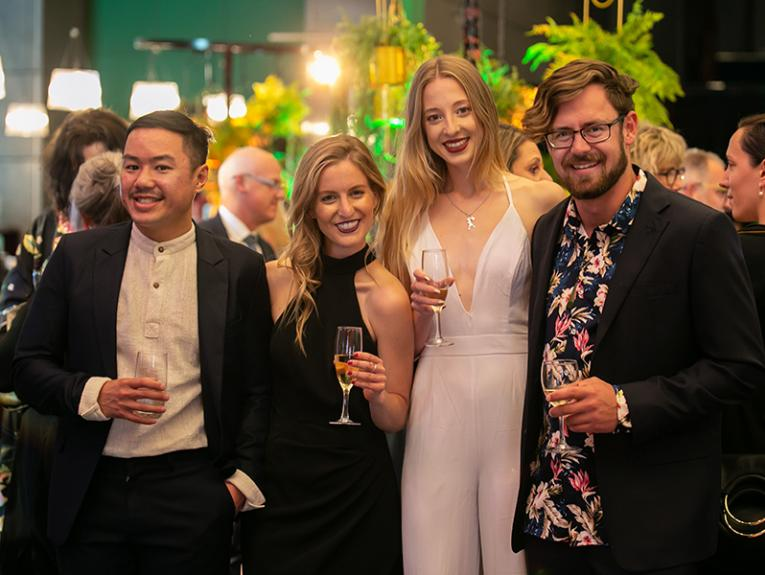 A group of people enjoy themselves at a cocktail party, smiling at the camera