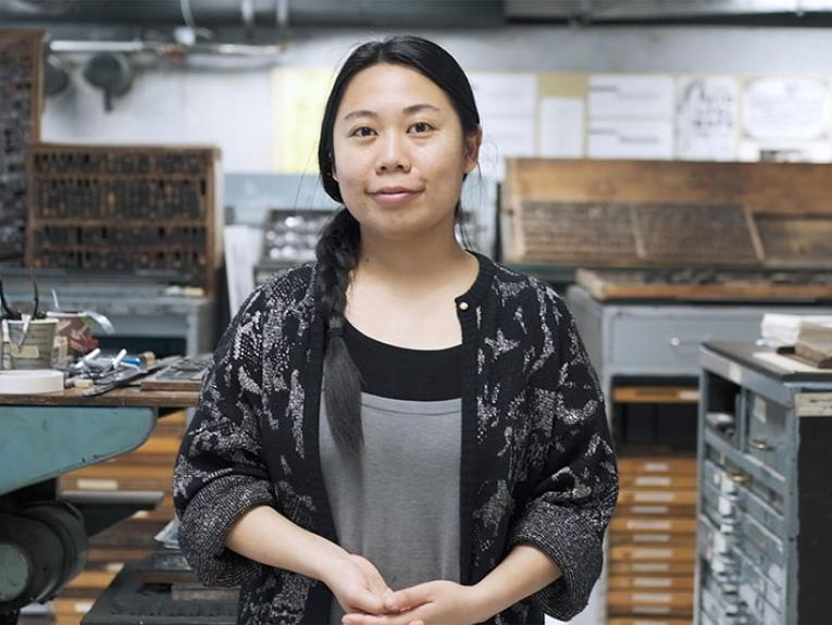 A woman stands in a printing press room looking directly at the camera