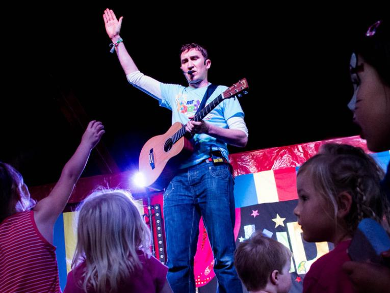 Man on stage with a guitar, small children are in front of the stage with their hands in the air