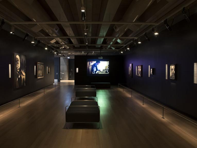 View of exhibition space with artworks lining the walls on the left and right and a film projected onto the back wall