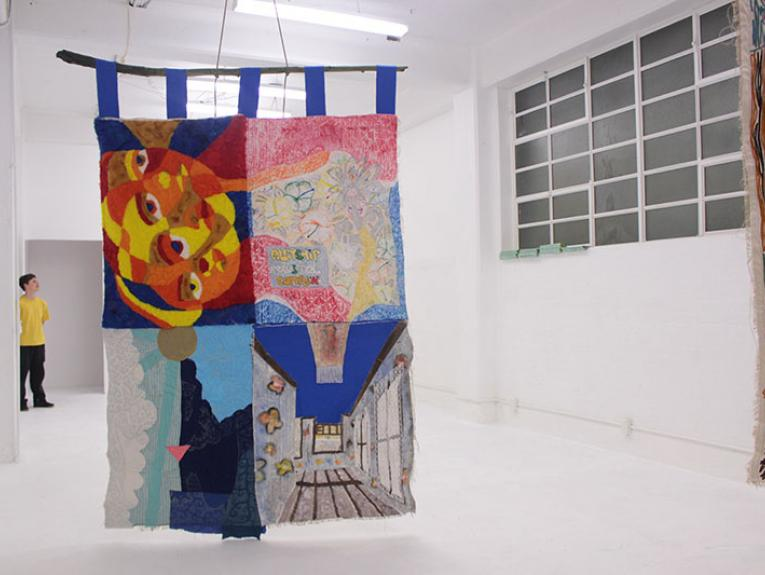 A large quilt hangs from the ceiling of the play_station gallery. It is an almost empty, white space. Part of another quilt can be seen hanging to the right of the frame