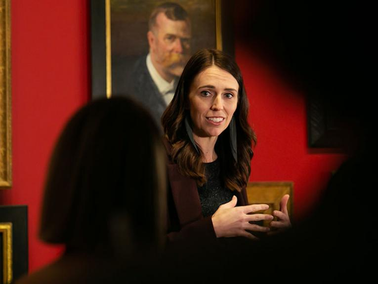 Close up of Jacinda Ardern addressing a crowd in front of the portrait wall in Toi Art