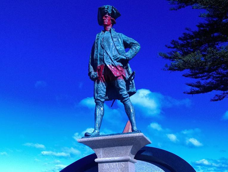 Statue of Captain James Cook with red paint on his face and across his abdomen