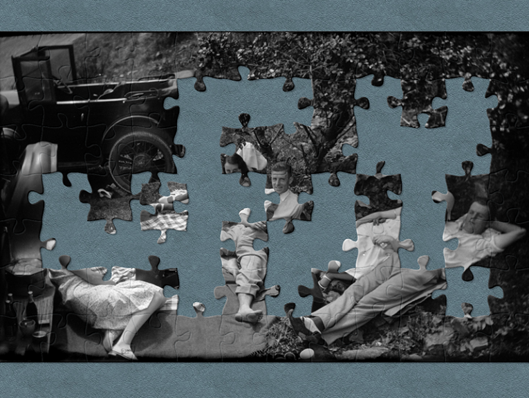 A black and white photo of five people lying on blankets having a picnic in the 1930s, they are surrounded by cars. There are jigsaw-shaped pieces missing from the image