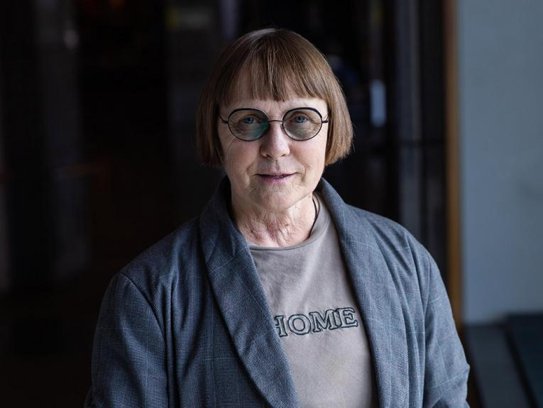 A photo of a woman wearing glasses in a dark hallway