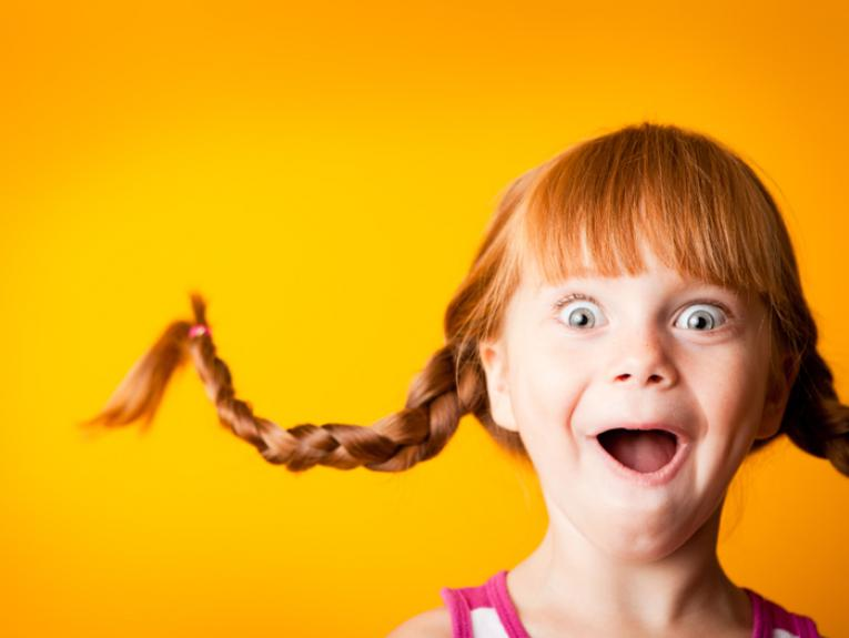 A little girl with pigtails jumping in the air