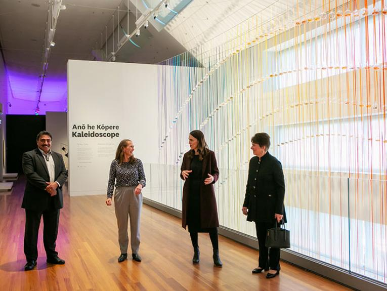 Four people stand talking in an art gallery with a large rainbow of colours behind them