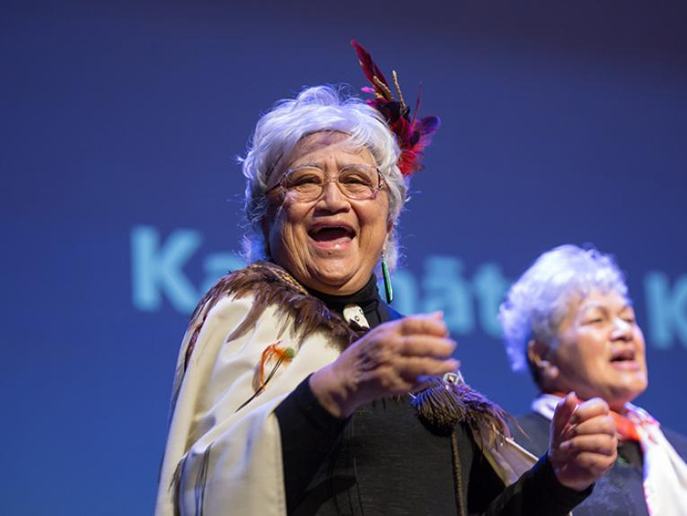 A lady in a Māori cloak sings