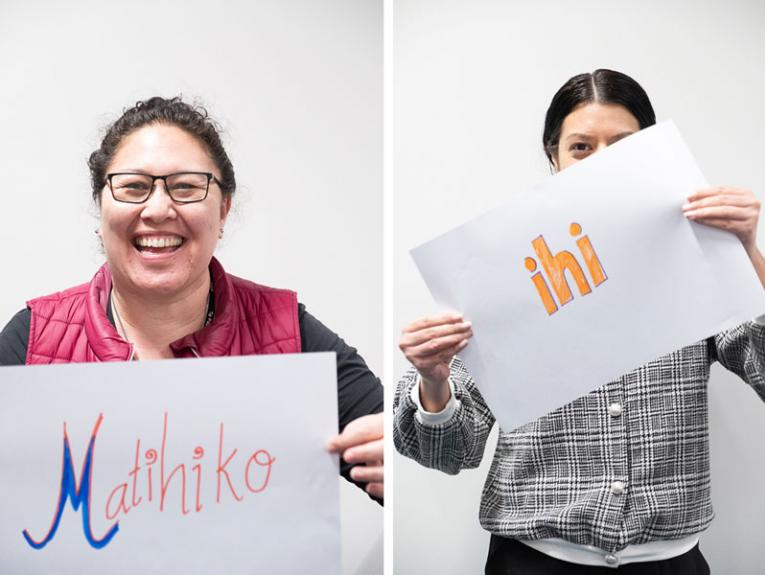 Two ladies holding up signs with Māori words 'ihi' and 'Matihiko' on them