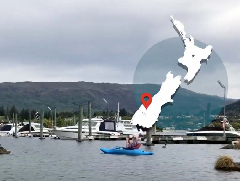 People in boats on a lake with a map of New Zealand overlaid on the right-hand side