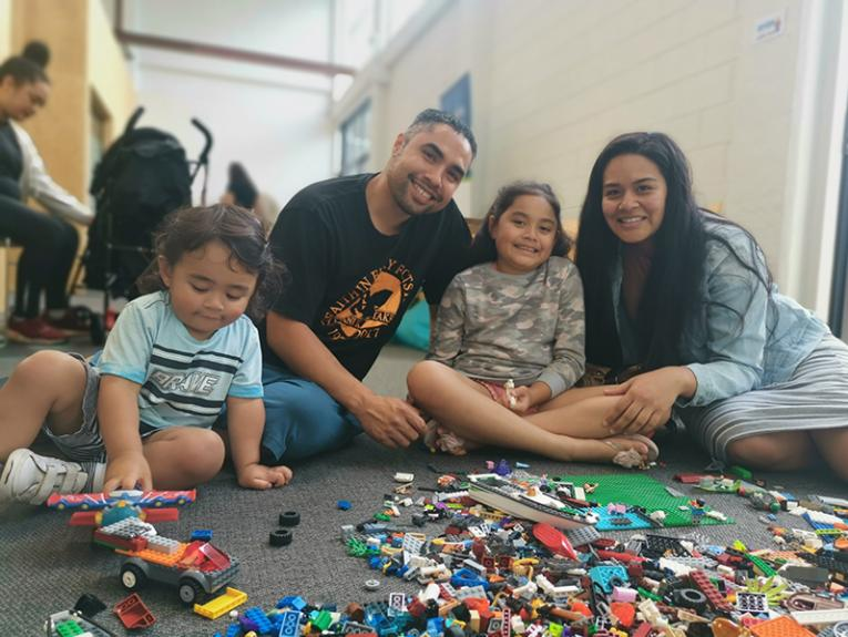A family sitting on the floor with lego blocks sitting in front of them.