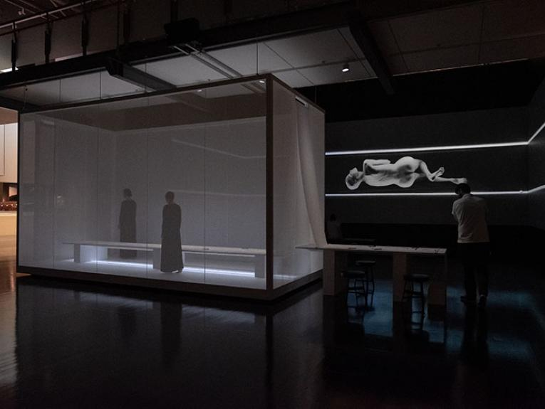 A man walks around a space that contains a box with two women inside and a massive projection on the wall of a woman contorting her body