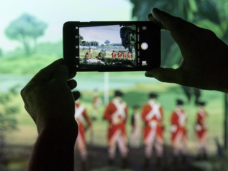 Close up of a person taking a photograph of Lisa Reihana's Emissaries, focusing on the screen of the camera