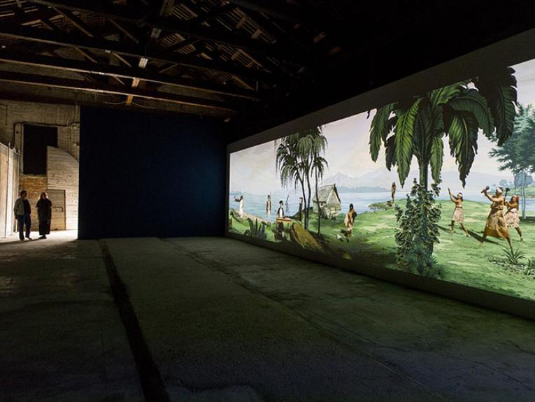 Two people look at Lisa Reihana's Emissaries artwork displayed at Venice Biennale