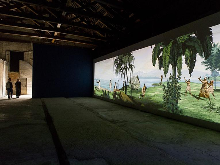 Two people look at Lisa Reihana's Emissaries artwork displayed at Venice Biennale