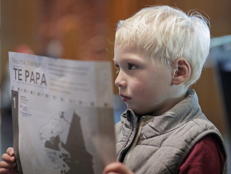 A little boy holds a Te Papa map