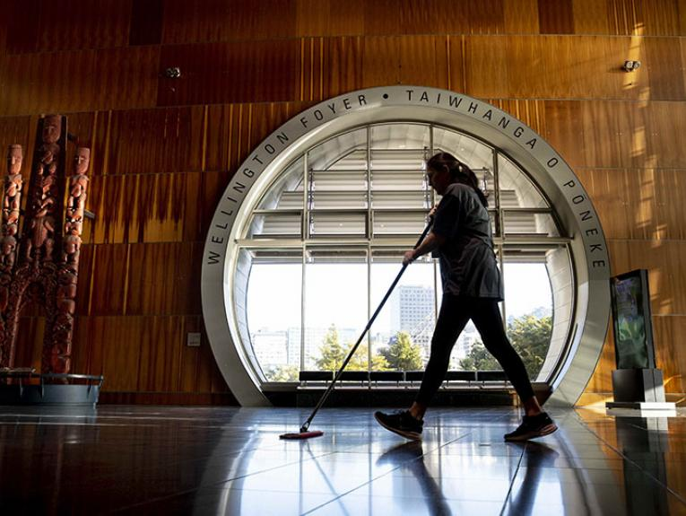 A woman wiping the floor passes a large round window in the Te Papa foyer