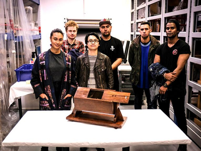 People pose for a photo behind a table on which sits a wooden ballot box