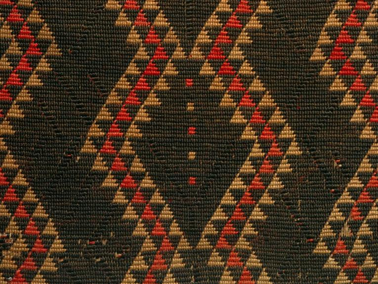 Close up of a cloak, showing the detail of its design. It is predominantly black with red and earth coloured triangles forming a wave across the cloak