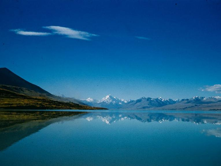 Photo of Lake Pukaki, with mirror-like water, and a view or Aoraki Mt Cook in the distance