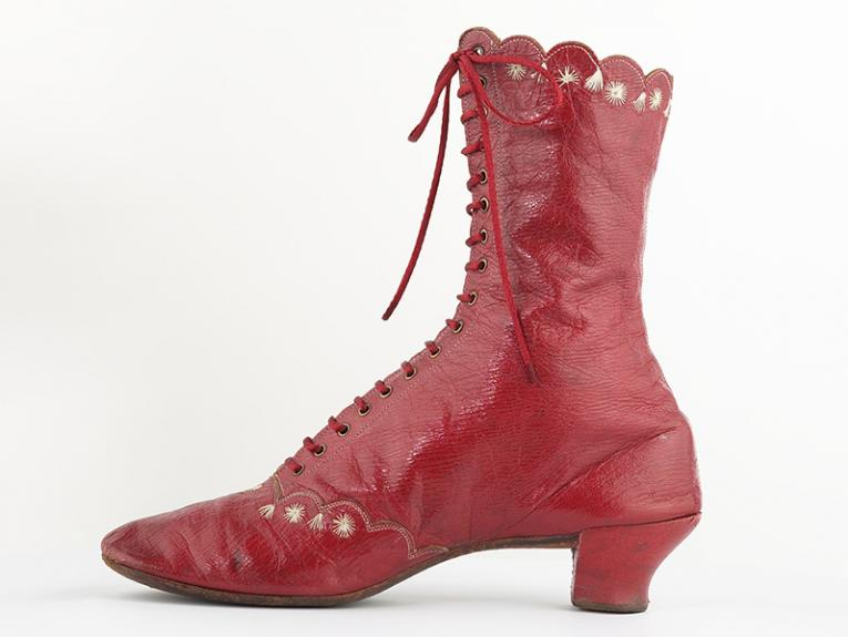 A single red boot viewed side-on with a white background