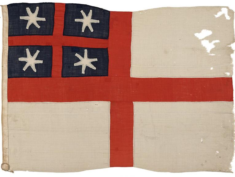 Weathered flag. It comprises of a white background with a red symmetric cross and in the top left quadrant a blue background with a smaller red symmetric cross and white stars in the quadrants