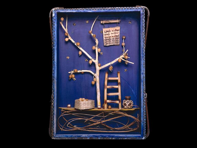 A blue box containing a wooden tree with apples, a ladder to climb to the branches, a basket for the apples, and a sign repeating uno/una in dieci (Italian for one in ten)