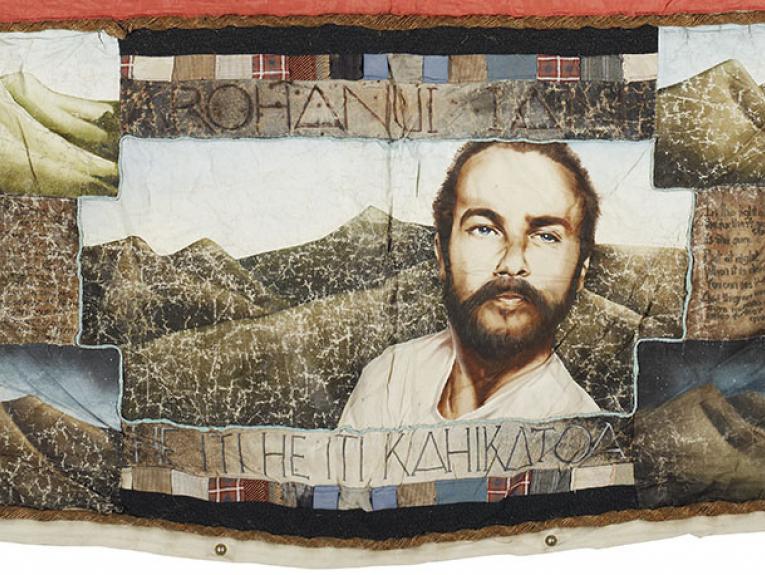 Panel of a quilt showing a portrait of a man and various scenes of mountains. It reads Arohanui Ian, He iti he iti kahikatoa