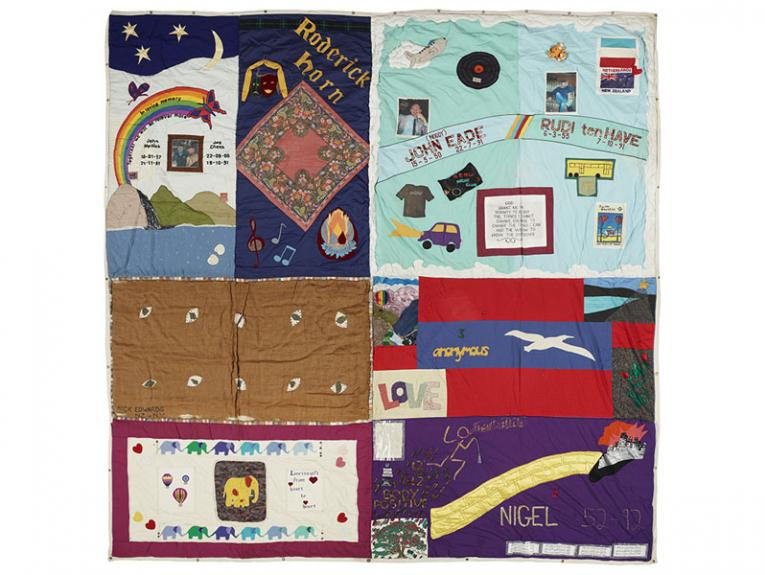 Quilt consisting of 8 vividly coloured panels dedicated to people who died of AIDS. Each panel contains a mixture of words and pictures