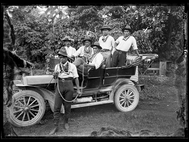 five men in cowboy outfits in an old car and one man in a cowboy outfit standing next to the car