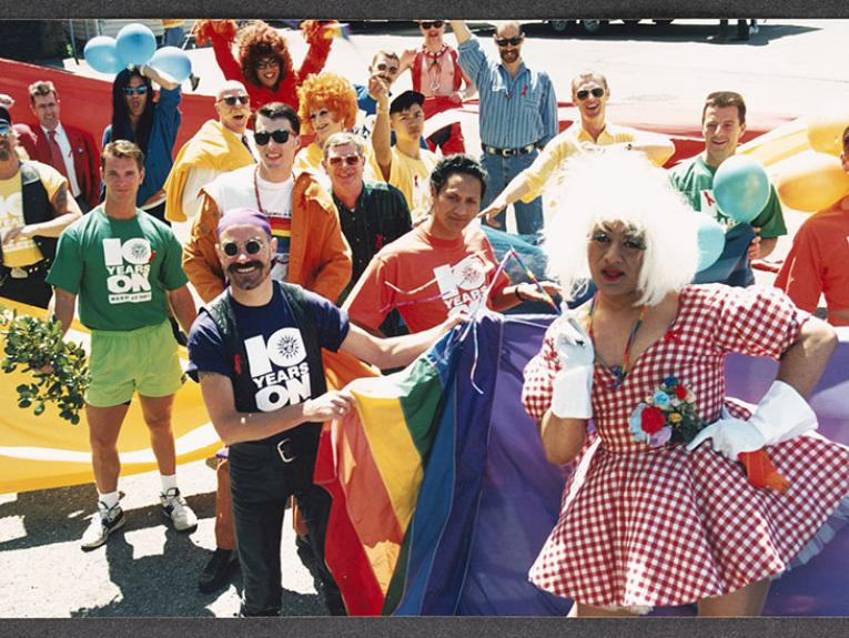 Group of people in an assortment of of costumes stand in a parade holding the rainbow flag