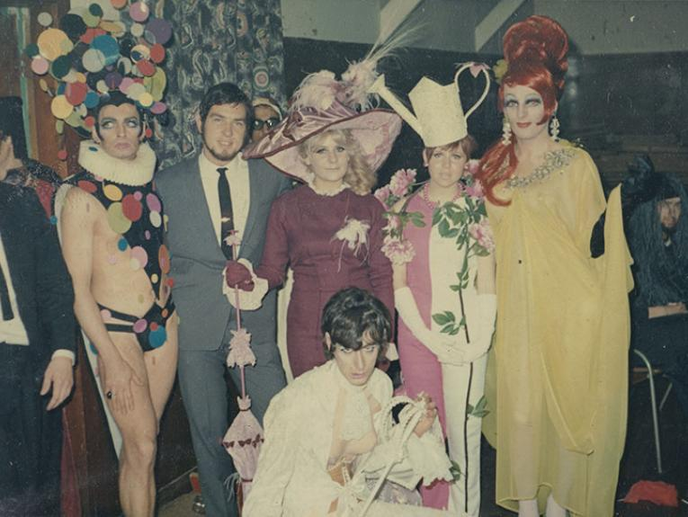Group of people in flamboyant costume in an array of colours and styles pose for a photo