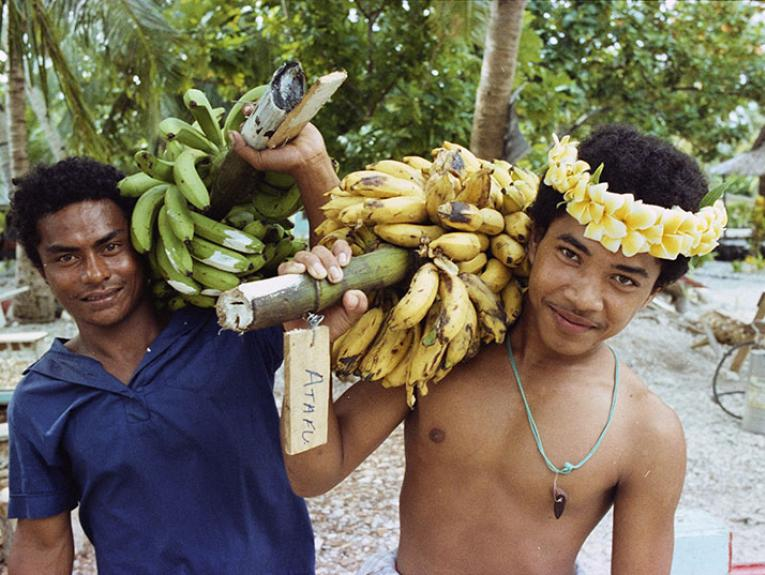 Two men holding bunches of bananas balanced on their shoulders pose for a photo