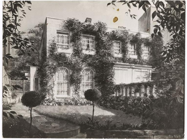 Photo of a large house, with creepers growing on its facade, and large windows. A manicured lawn is in front of the house