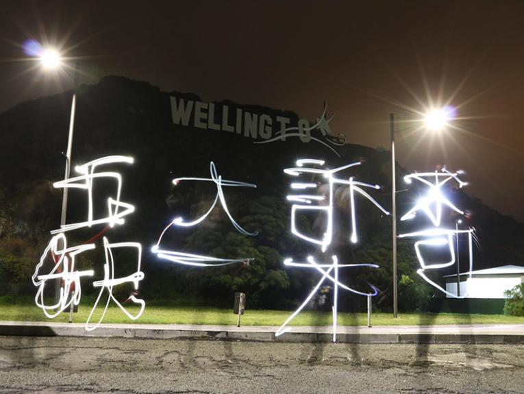 A photo of someone writing Chinese using light outside in the dark