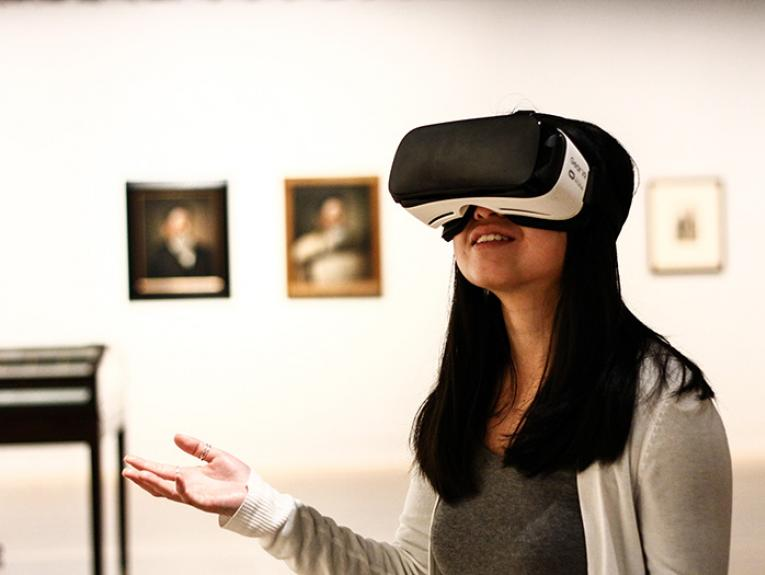 A woman wears a VR headset in an art gallery