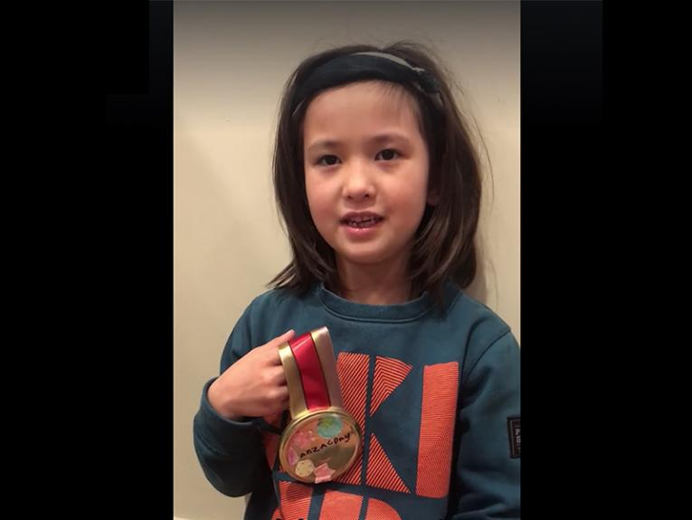 A young girl in a sweatshirt inside a house holding a homemade medal