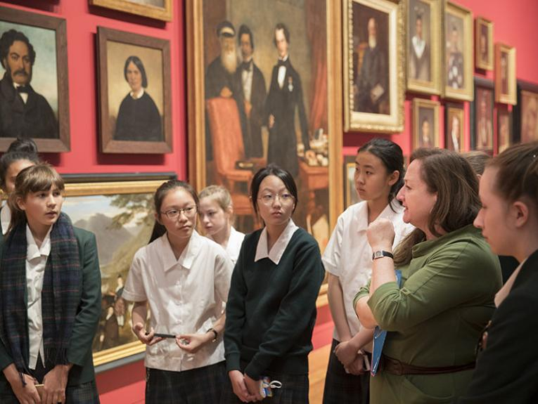 Students and a teacher stand in front of a wall of paintings