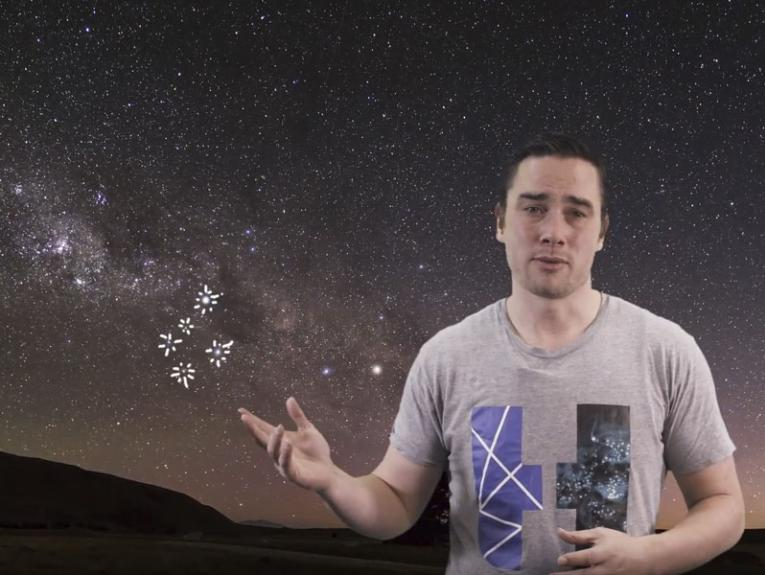 A man stands in front of a picture of the night sky
