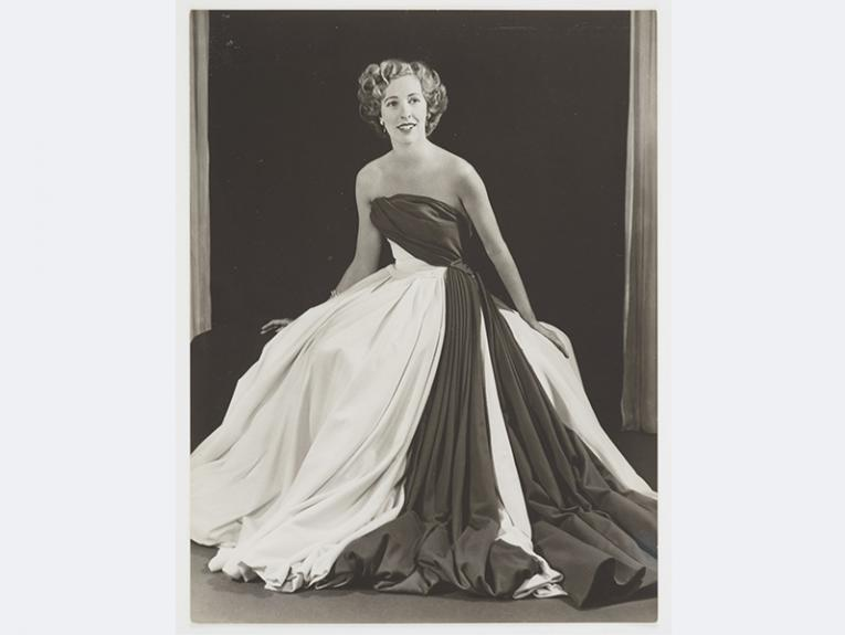 A black and white photo of a woman in a long dress
