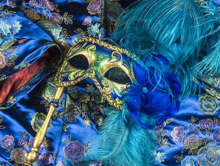 Venetian-style masquerade mask sits on top of a blue jacket