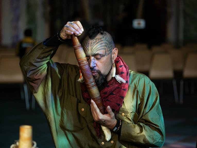 A man holding a long wooden musical instrument up to his mouth and blowing through it