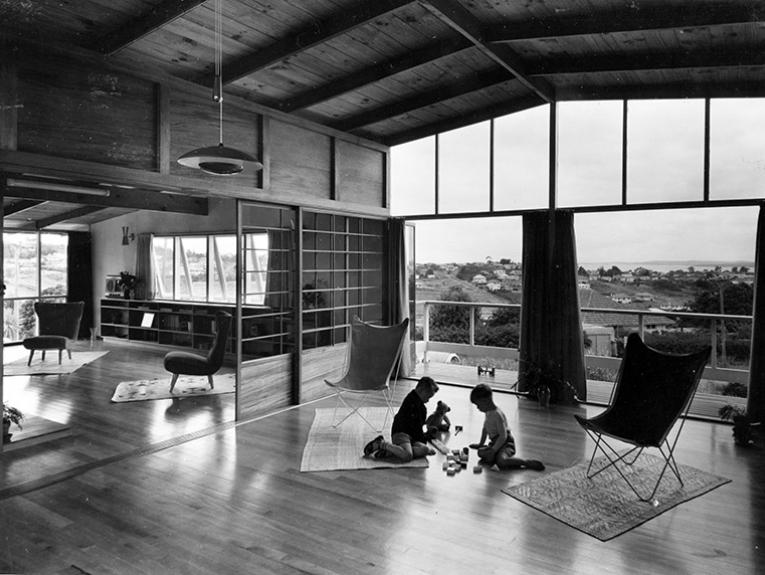 Black and white photo of two children playing on the floor in a big room with a view of other houses and the harbour.
