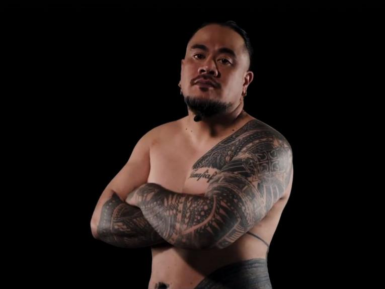 A man with Sāmoan tattoos stands with his arms crossed