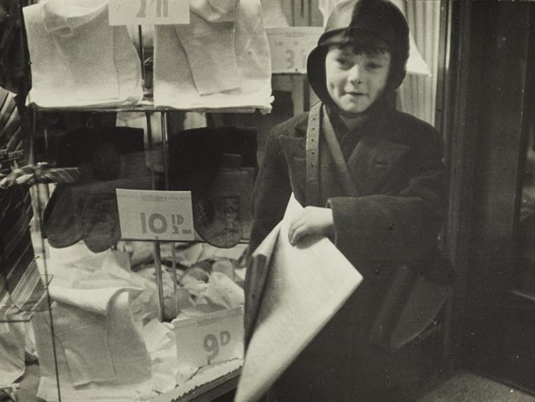 A boy holds newspapers, in a 1938 photograph