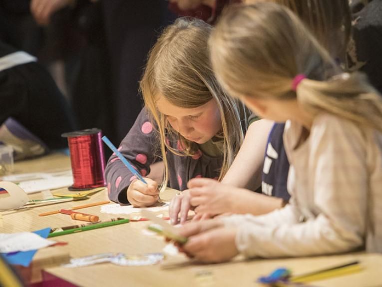 Children draw with coloured markers at a craft table
