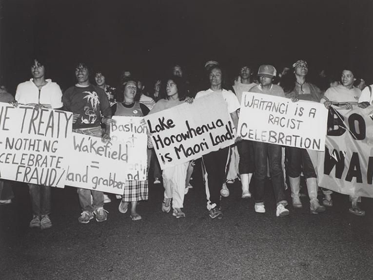 """Group of protestors holding signs – one example says """"Waitangi is a racist celebration"""" – march towards the camera"""