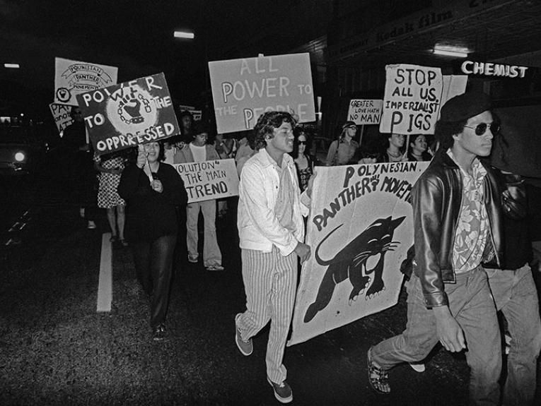 A group of people march in a line holding placards
